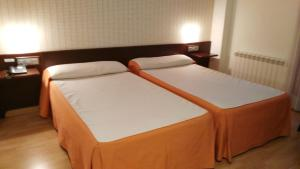 A bed or beds in a room at Hotel Alfageme