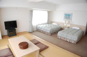 A bed or beds in a room at Aomori Winery Hotel