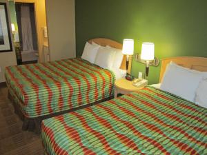 A bed or beds in a room at Extended Stay America Suites - Orlando - Lake Buena Vista