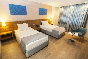 A bed or beds in a room at Fesa Business Hotel