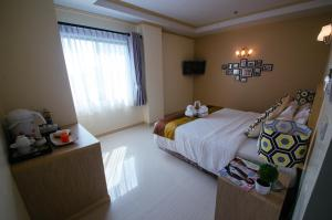 A bed or beds in a room at Thipurai City Hotel