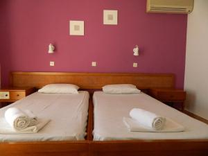 A bed or beds in a room at Telhinis Hotel