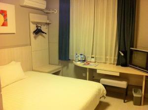 Кровать или кровати в номере Jinjiang Inn Dezhou Railway Station