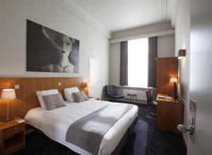 A bed or beds in a room at Theater Hotel Leuven Centrum