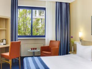 A bed or beds in a room at IntercityHotel Nürnberg