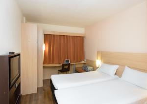 Cama ou camas em um quarto em ibis Salvador Rio Vermelho