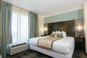 A bed or beds in a room at Wingate By Wyndham - Orlando International Airport
