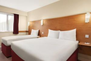 A bed or beds in a room at Days Inn Warwick Northbound M40