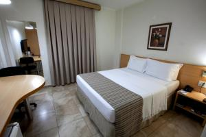 A bed or beds in a room at Oitis Hotel