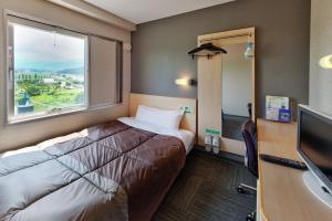 A bed or beds in a room at Super Hotel Arai Niigata