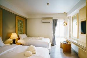 A bed or beds in a room at Moon Dragon Hotel