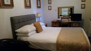 A bed or beds in a room at The Royal Hotel Tain