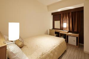 A bed or beds in a room at UNIZO INN Sapporo