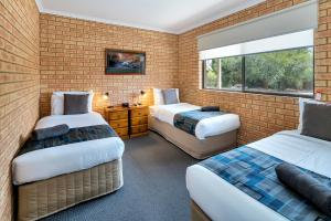 A bed or beds in a room at Begonia City Motor Inn
