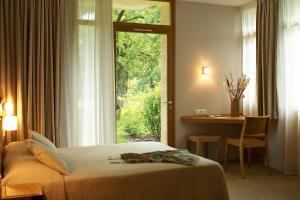 A bed or beds in a room at Hôtel Les Esclargies