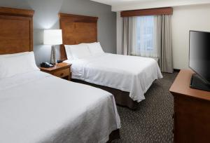 A bed or beds in a room at Homewood Suites by Hilton Omaha - Downtown