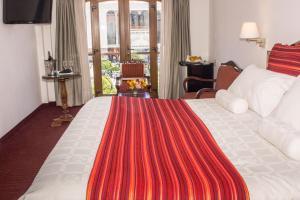 A bed or beds in a room at Hotel Hacienda Plaza de Armas
