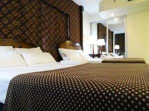 A bed or beds in a room at Abasto Hotel