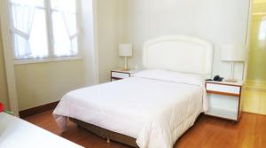 A bed or beds in a room at Pousada Magister
