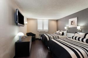 A bed or beds in a room at Ramada Plaza by Wyndham West Hollywood Hotel & Suites