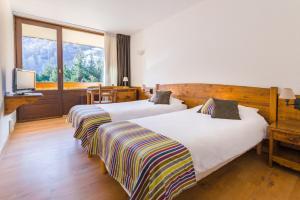 A bed or beds in a room at Hôtel Plein Sud et piscine ***
