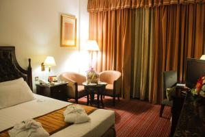 A bed or beds in a room at Grand Mayfair Hotel