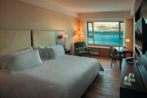 A bed or beds in a room at Arakur Ushuaia Resort & Spa