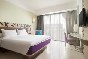 A bed or beds in a room at Ibis Styles Bali Benoa