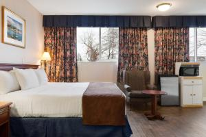 A bed or beds in a room at Days Inn by Wyndham Brockville