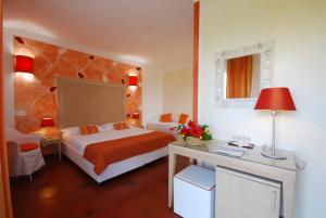 A bed or beds in a room at Cala Rosa Club Hotel