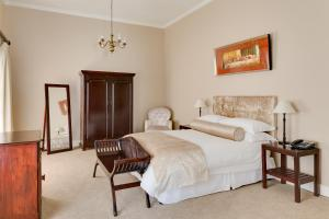 A bed or beds in a room at Protea Hotel by Marriott Dorpshuis & Spa Stellenbosch