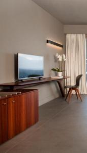 A television and/or entertainment centre at Tui Blue Elounda Village Resort & Spa by Aquila