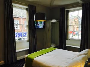 A bed or beds in a room at The King's Head Hotel Wetherspoon