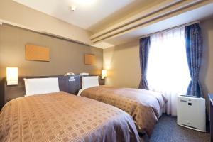 Tempat tidur dalam kamar di Hotel Sunroute Sapporo