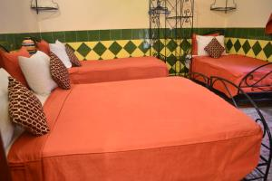 A bed or beds in a room at Riad Hôtel Belleville Marrakech