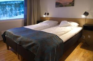 A bed or beds in a room at Hamarøy Hotel