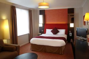 A bed or beds in a room at The Dragon Hotel