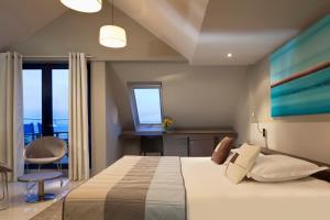 Un ou plusieurs lits dans un hébergement de l'établissement Hostellerie Pointe St-Mathieu,The Originals Collection