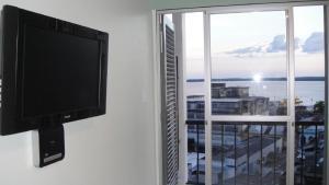 Una televisión o centro de entretenimiento en Ajuricaba Suites 1
