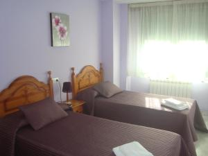A bed or beds in a room at Pensión Plaza