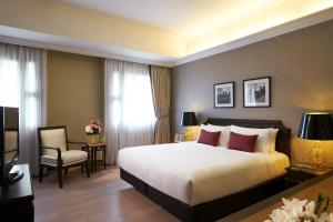 A bed or beds in a room at Orchard Parksuites by Far East Hospitality