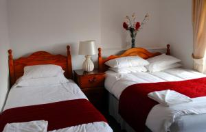 A bed or beds in a room at The Queens Head Hotel