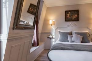 A bed or beds in a room at Hôtel De La Porte Dorée