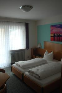 A bed or beds in a room at Hotel Restaurant zur Windmühle