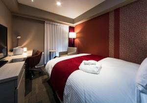 A bed or beds in a room at Daiwa Roynet Hotel Kokura Ekimae