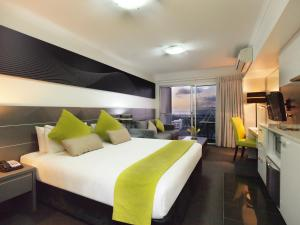 A bed or beds in a room at Oaks Townsville Metropole Hotel