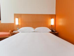A bed or beds in a room at Ibis Abu Dhabi Gate