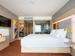 A bed or beds in a room at Novotel Manila Araneta City Hotel