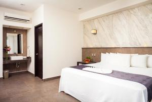A bed or beds in a room at Aspira Hotel & Beach Club