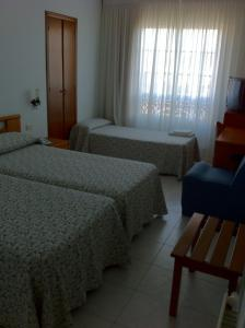 A bed or beds in a room at Hotel Pinzon